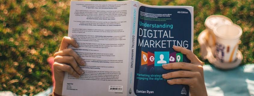reading digital marketing book on grass